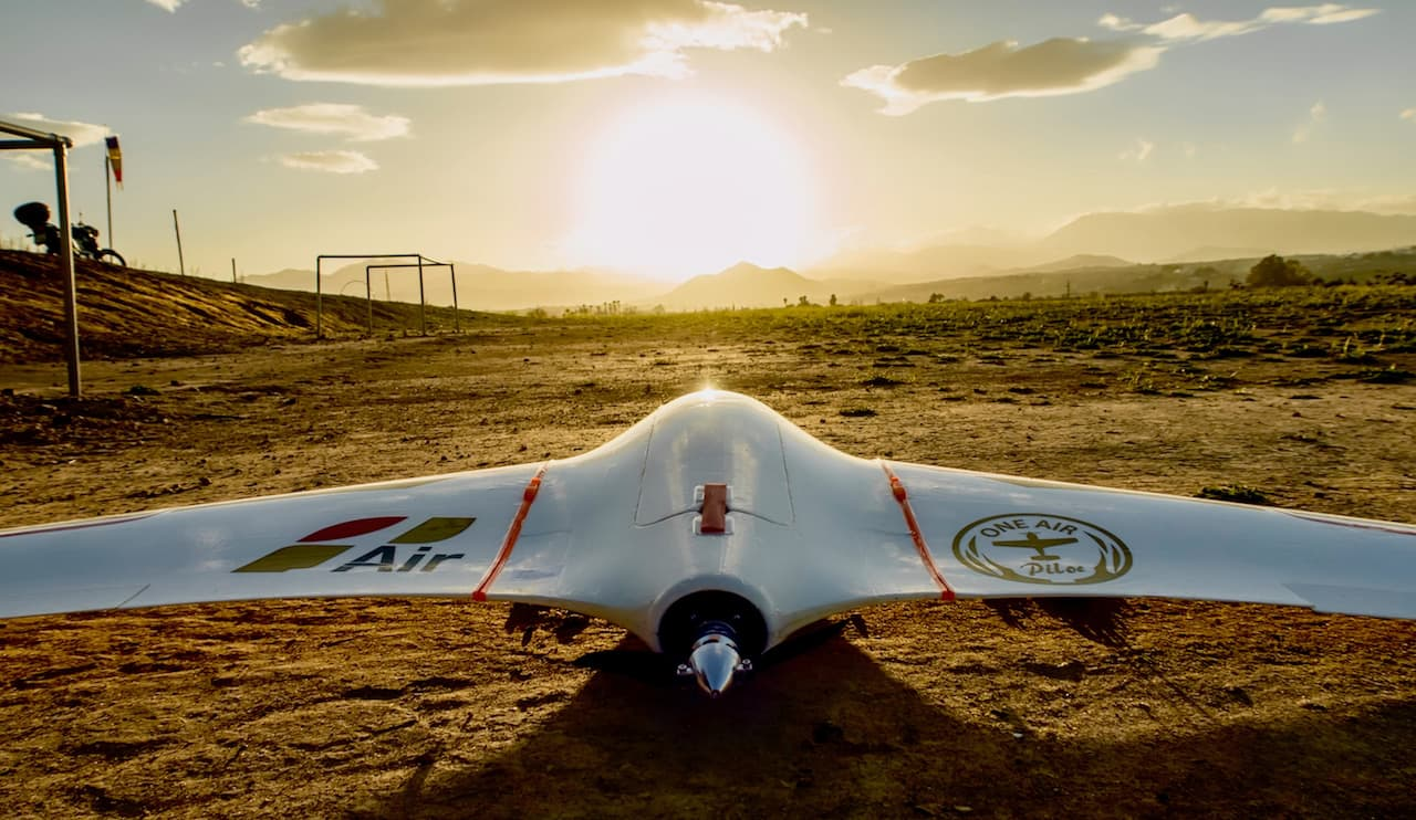 fixed wing drone landed on the ground with the sun on a sunrise background