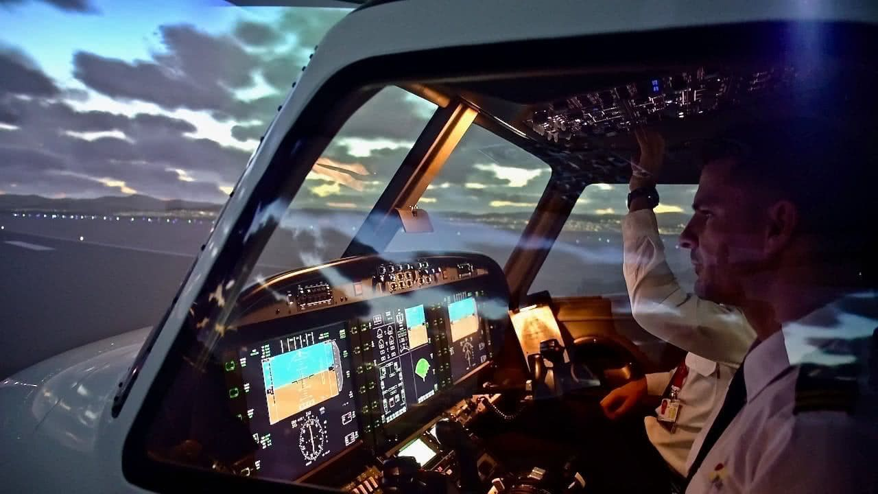 outside view of alsim alx simulator wtih two commercial pilot trianing