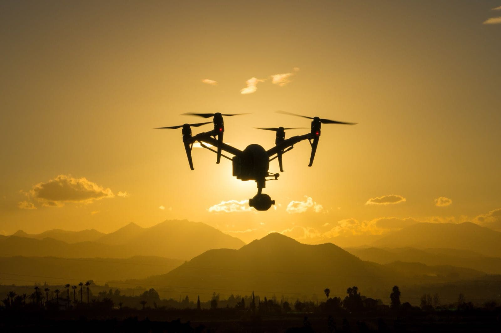 dji inspire 2 drone in flight with gradient orange background at sunset
