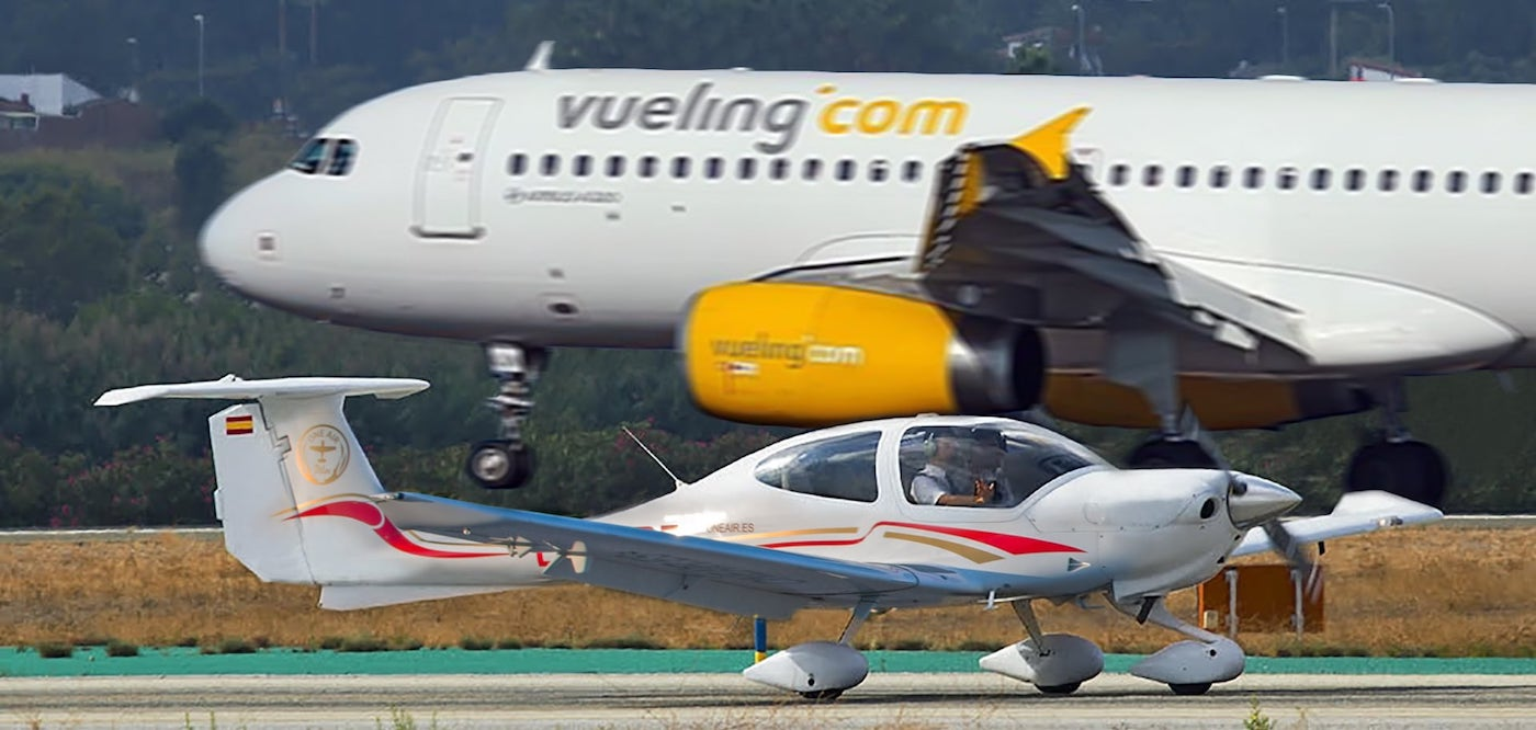 one airs diamond da42 at malagas international airport with a vueling plane in the background
