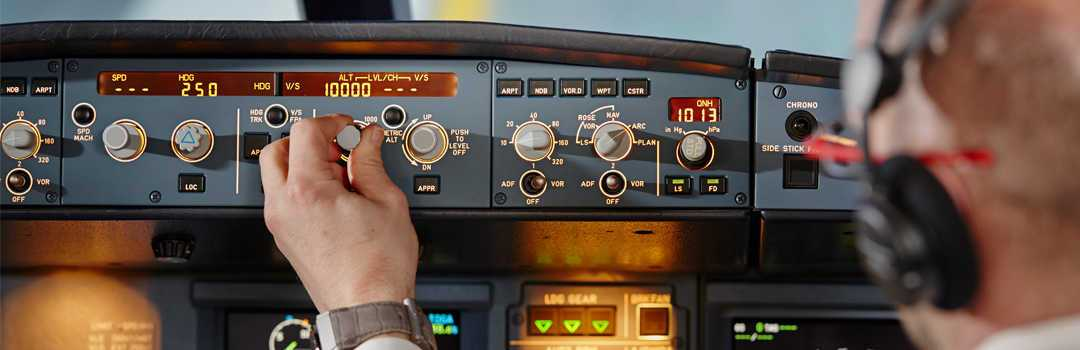 a pilot adjusting controls in a plane dashboard