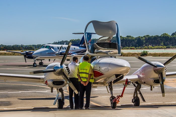 pilot and technician inspecting a diamond da42 aircraft from one air at the airport with plane in the background