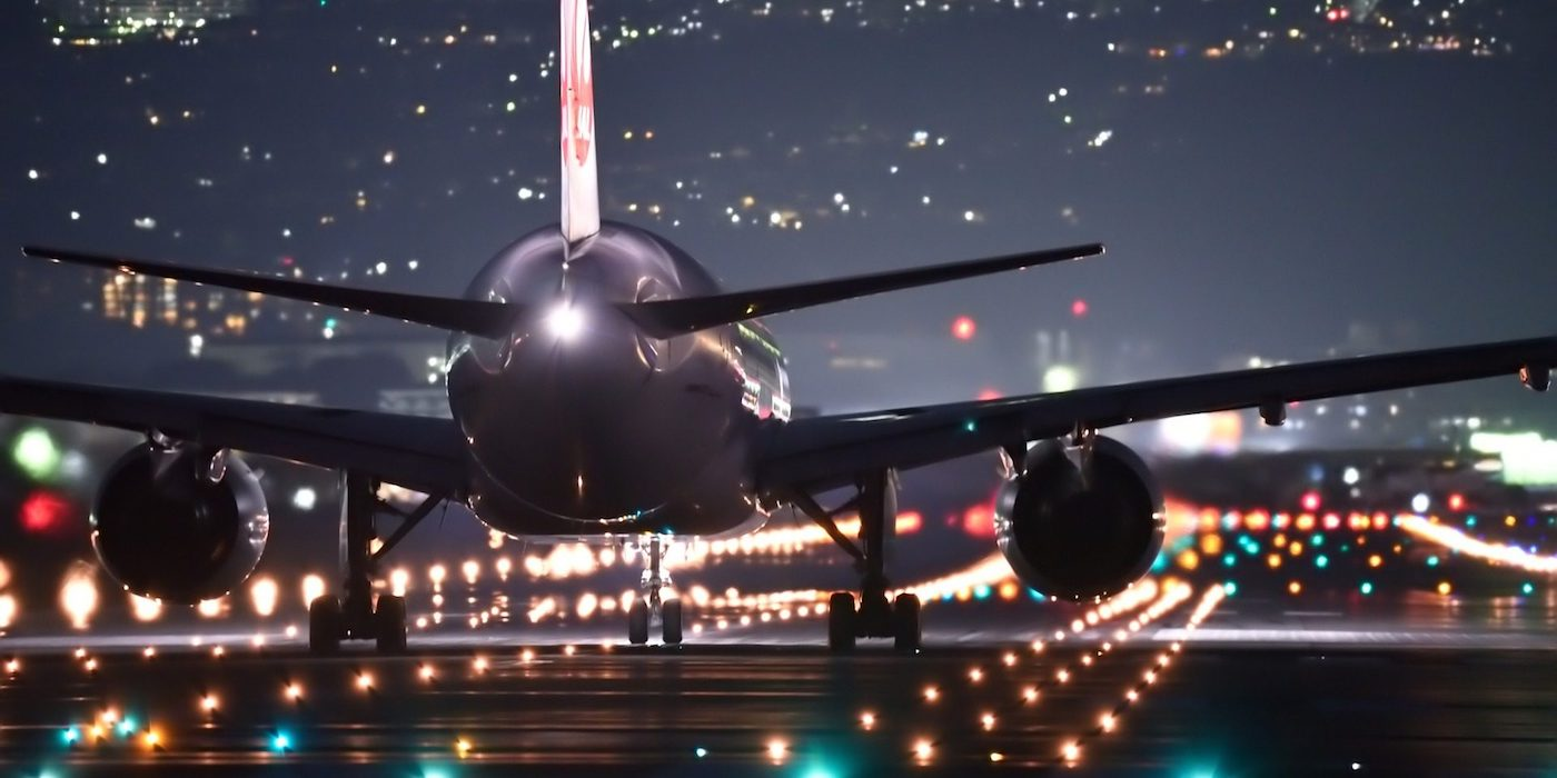 rear view of airplane moving forward runway illuminated at night