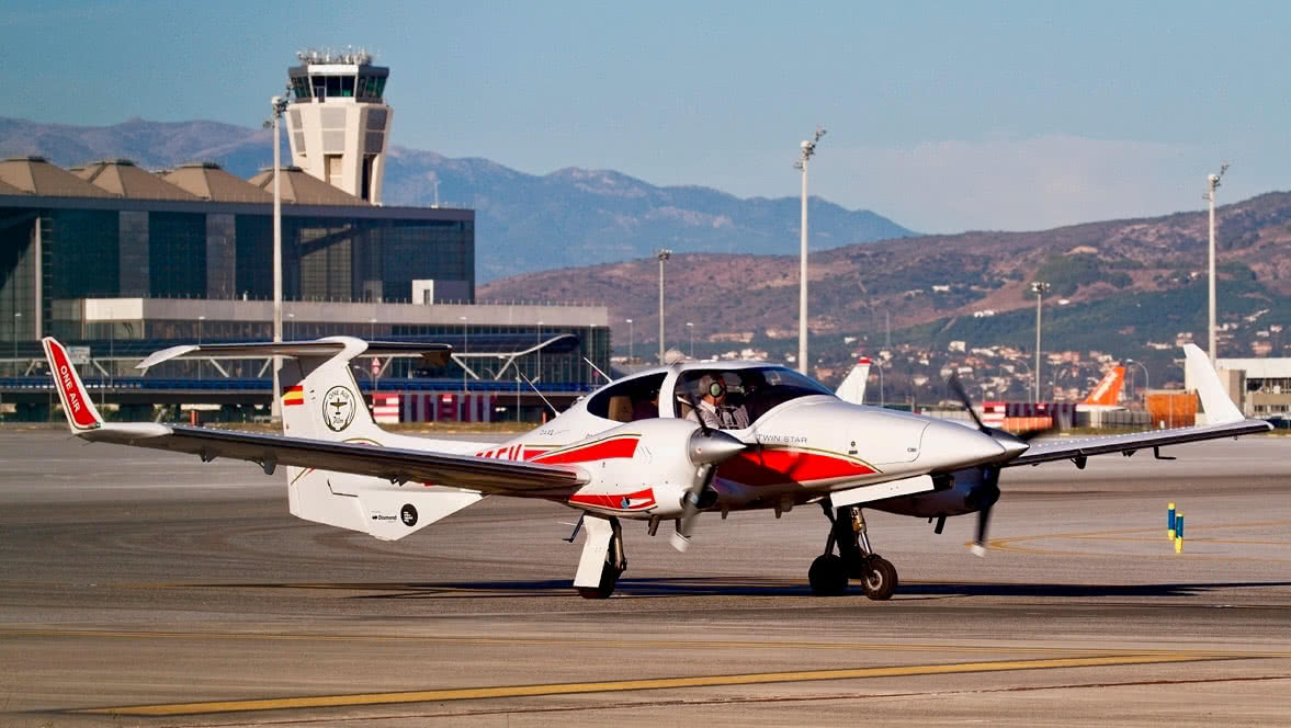 a oneairs diamond da42 al malagas international airport with control tower in the background