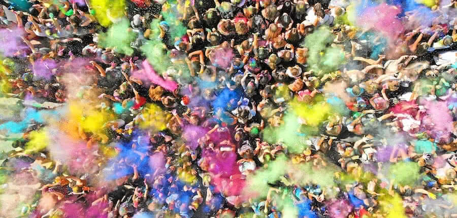a lot of people with color powder in an aerial view of holi colors festival