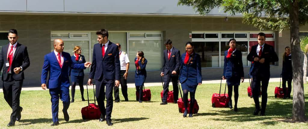 air hostess malaga students walking in the grass with blue and red uniform and air hostess suitcases
