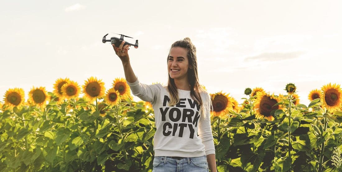 young woman holding a drone in a hand with sunflowers background and sunset golden light