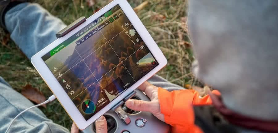 hands holding a rc controller with screen surveiying forest with drones
