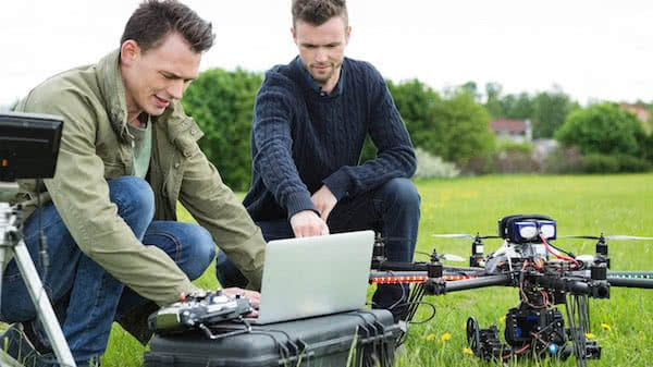 surveyors preparing industrial drone to mapping a land
