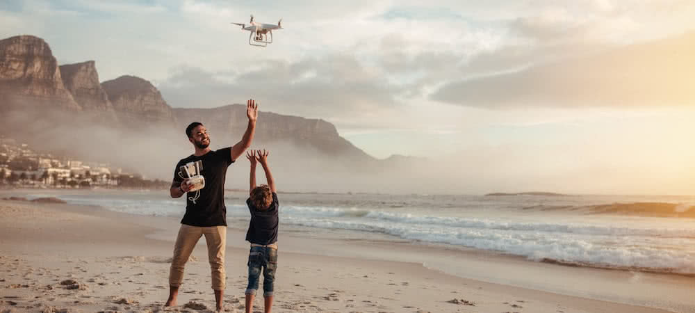 man fliying a drone with a child in the beach with golden light at sunset