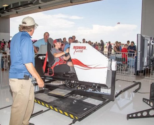 young man testing the full motion redbird xwind simulator in event with more people in the background
